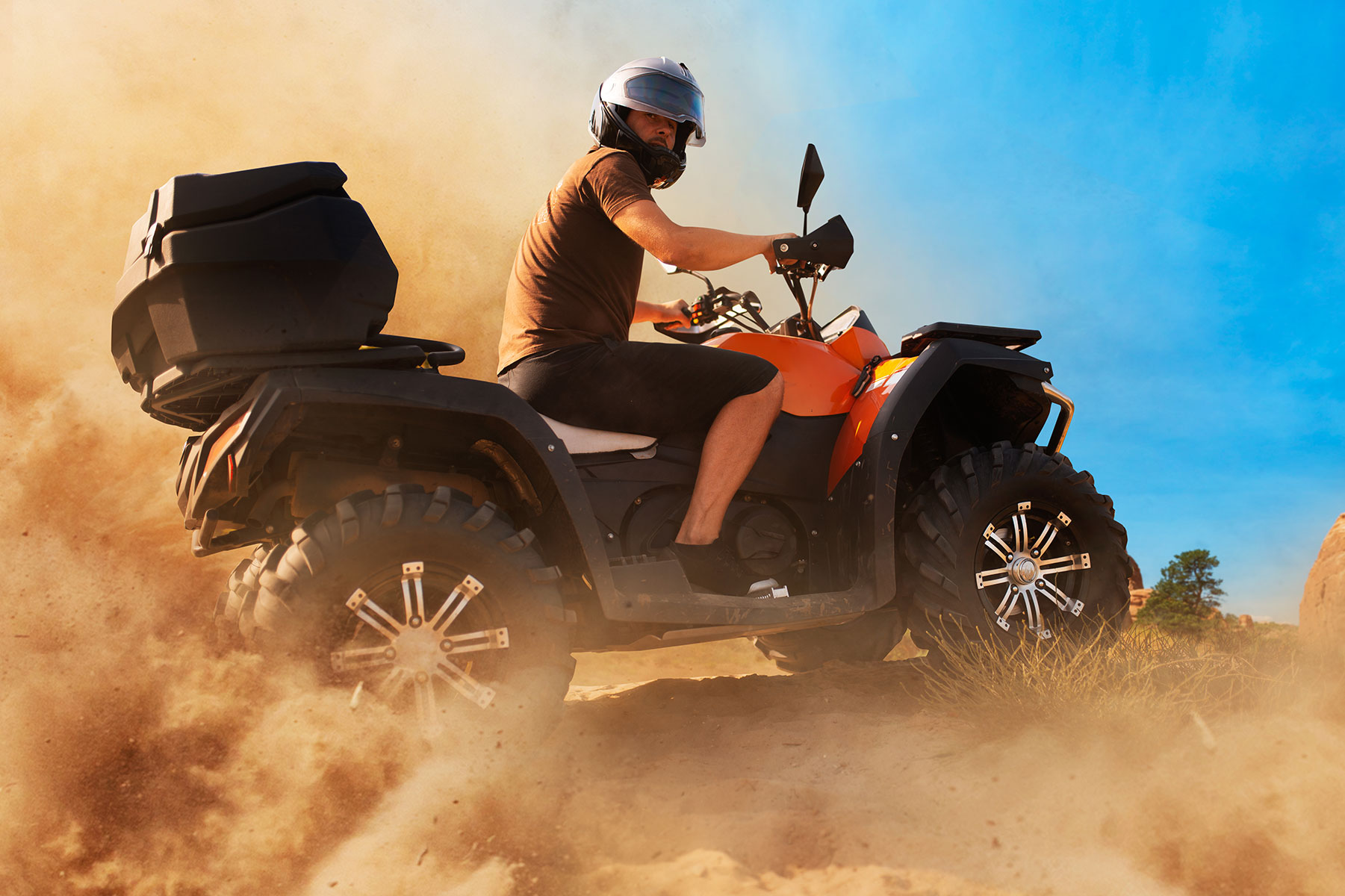 guy riding ATV in a plum of dust