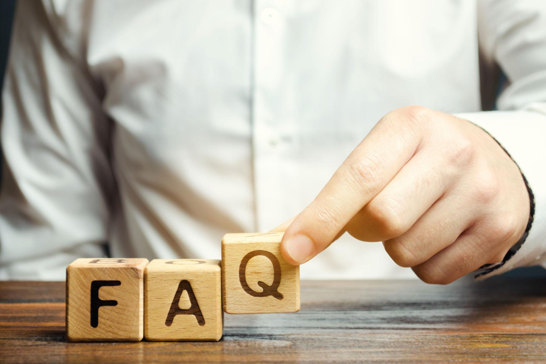 closeup of businessman putting wood blocks together to spell FAQ