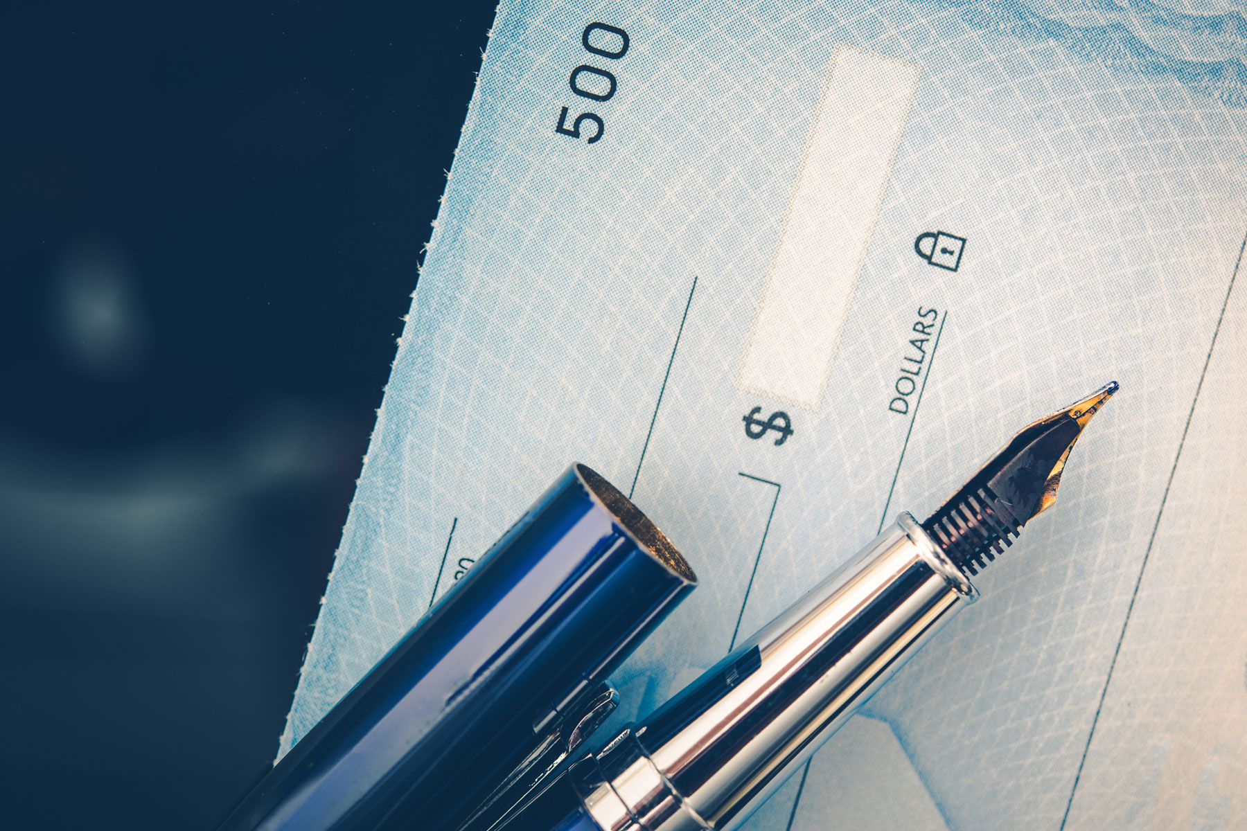 close up of a check and a pen