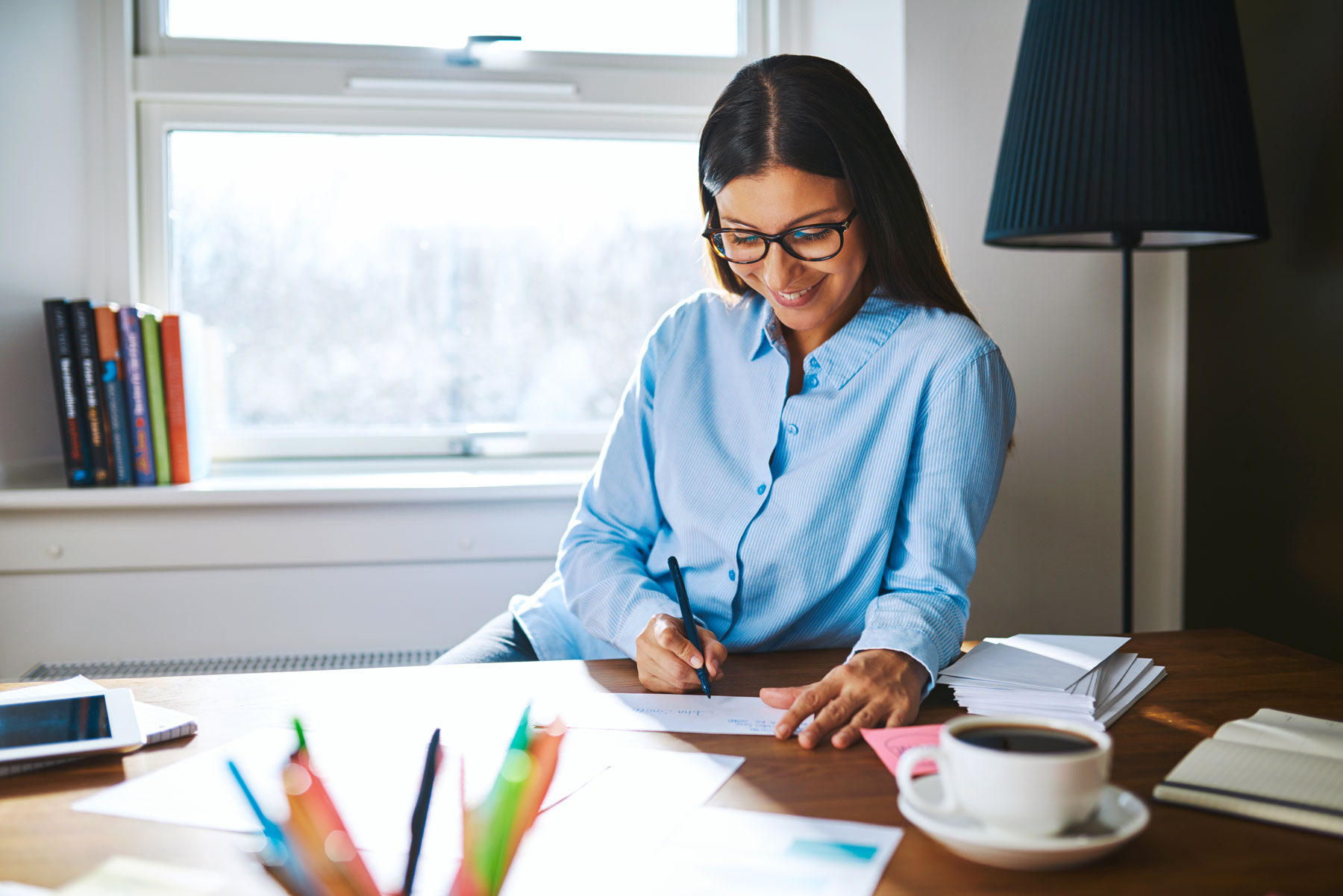 woman smiling and writing check