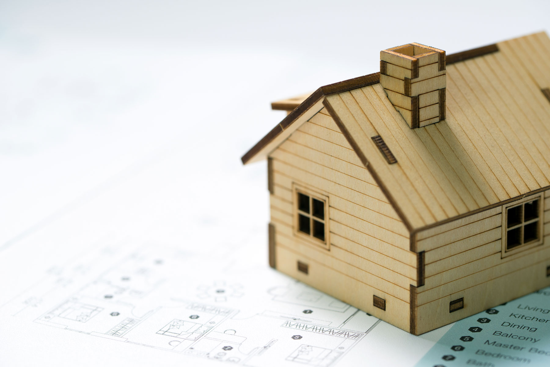small wooden model of house on top of blueprints