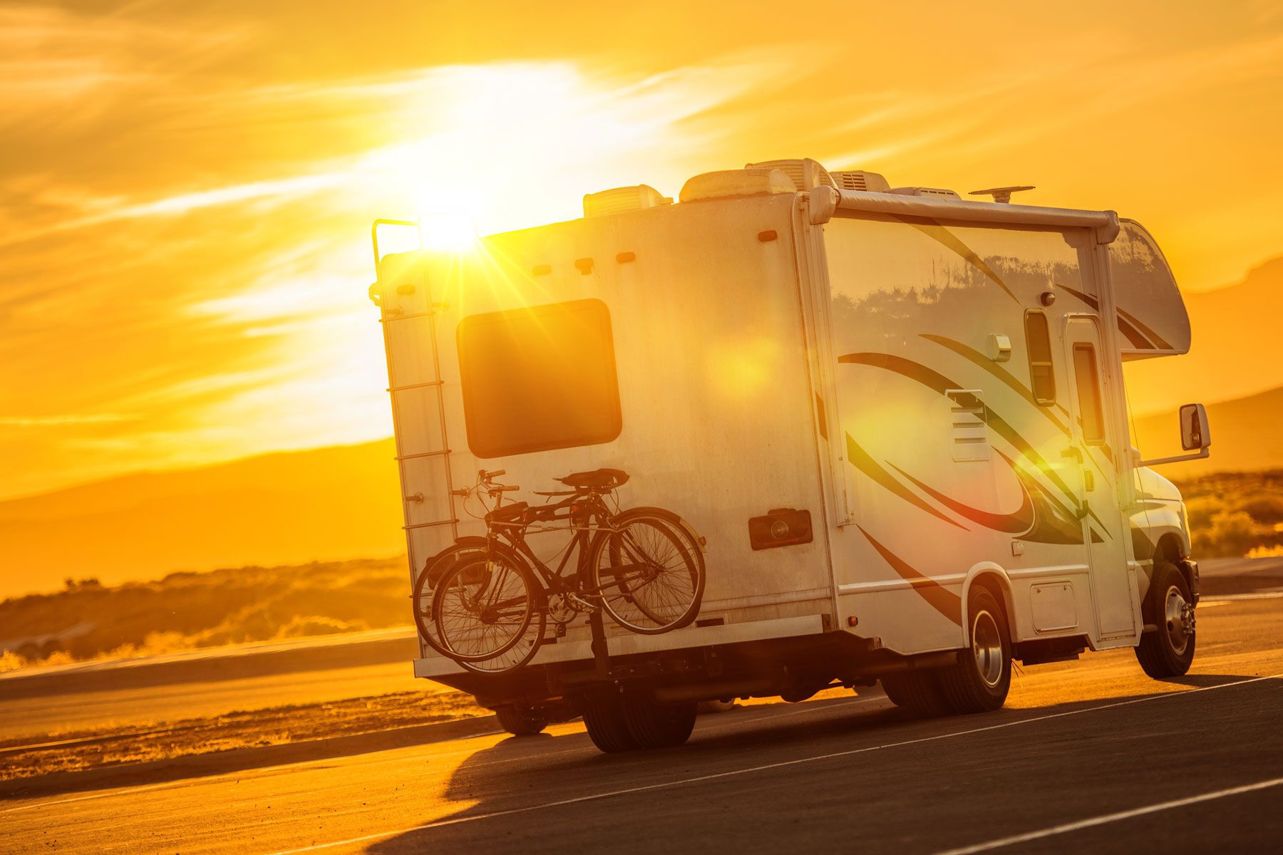 recreational vehicle driving into sunset