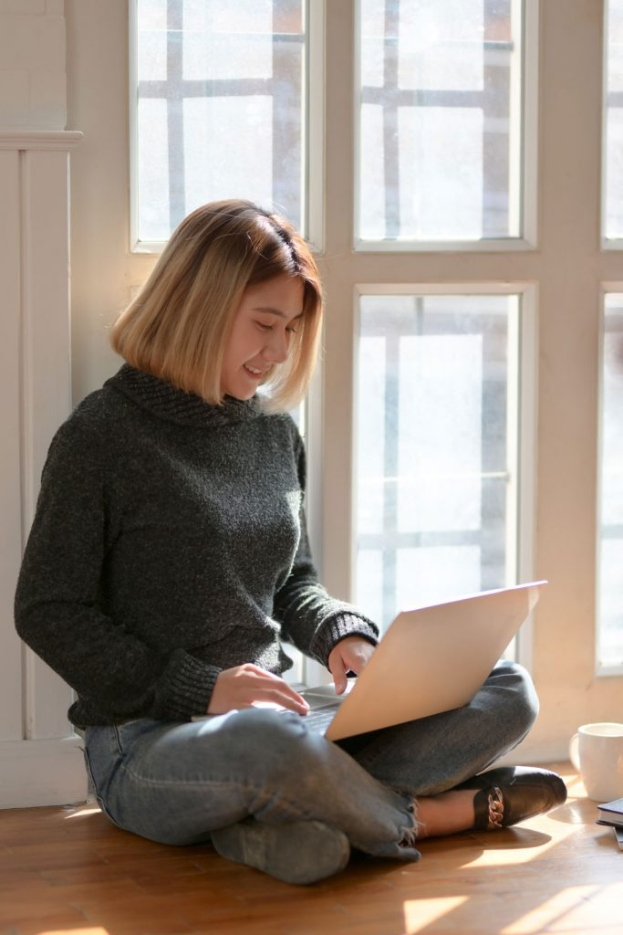 woman sitting in window reading FAQs on her computer